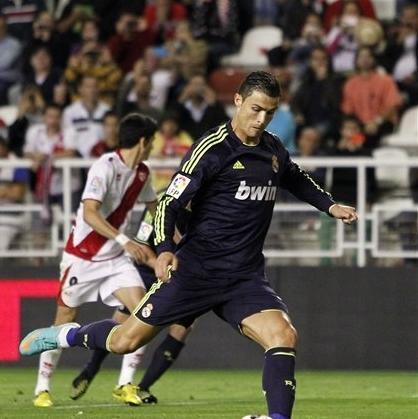 Real Madrid's Cristiano Ronaldo from Portugal, right, scores his goal during a Spanish La Liga soccer match against Rayo Vallecano at the Vallecas stadium in Madrid, Spain, Monday, Sept. 24, 2012. (AP Photo/Andres Kudacki)