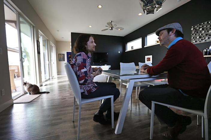 In this March 13, 2014 photo, Dave Mullins, left, and his husband Charlie Craig play cards and talk after a work day, at their home in Westminster, Colo. The couple filed a legal complaint with the Colorado Civil Rights Commission against a Denver-area baker who refused to make a wedding cake for the two men, based on his religious beliefs. The baker, Masterpiece Cakeshop owner Jack Phillips, is appealing a ruling by a judge in December 2013 which upheld the complaint, and orders the baker to serve gay couples despite his religious beliefs or face fines. (AP Photo/Brennan Linsley)