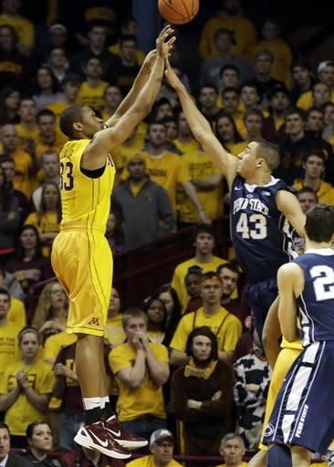 Minnesota's Rodney Williams, left, gets a shot off over Penn State's Ross Travis in the first half of an NCAA college basketball game, Saturday, March 2, 2013, in Minneapolis. (AP Photo/Jim Mone)