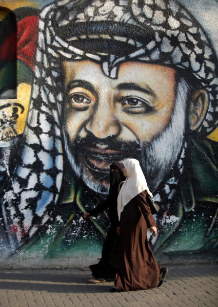 Palestinian women walk in front of a mural depicting the late Palestinian leader Yasser Arafat, in Gaza City, Monday, Nov. 11, 2013. Arafat died Nov. 11, 2004 at a French military hospital, a month after falling ill at his West Bank headquarters. (AP Photo/Hatem Moussa)