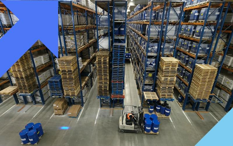 A warehouse worker moves barrels using a forklift - Yuriko Nakao/Bloomberg