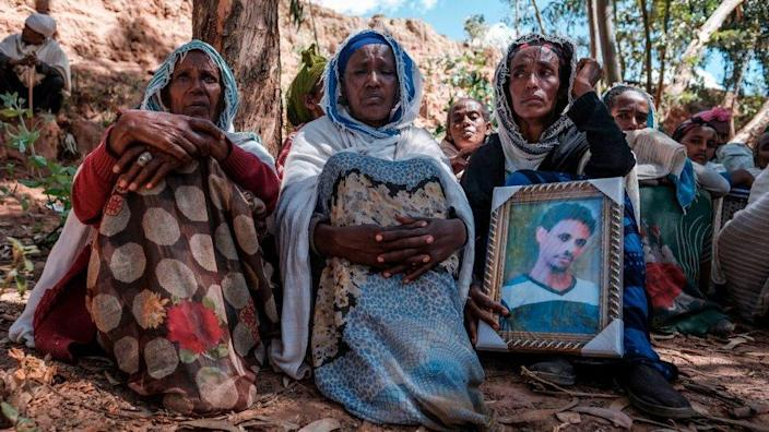 People mourn the victims of killings in the village of Dengolat in Tigray.