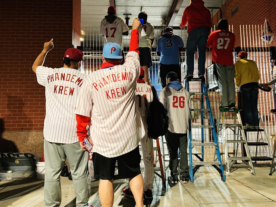 The Krew cheers from outside the gates in Philadelphia, taking turns on ladders to catch a glimpse of the field. (Photo by Hannah Keyser / Yahoo Sports)
