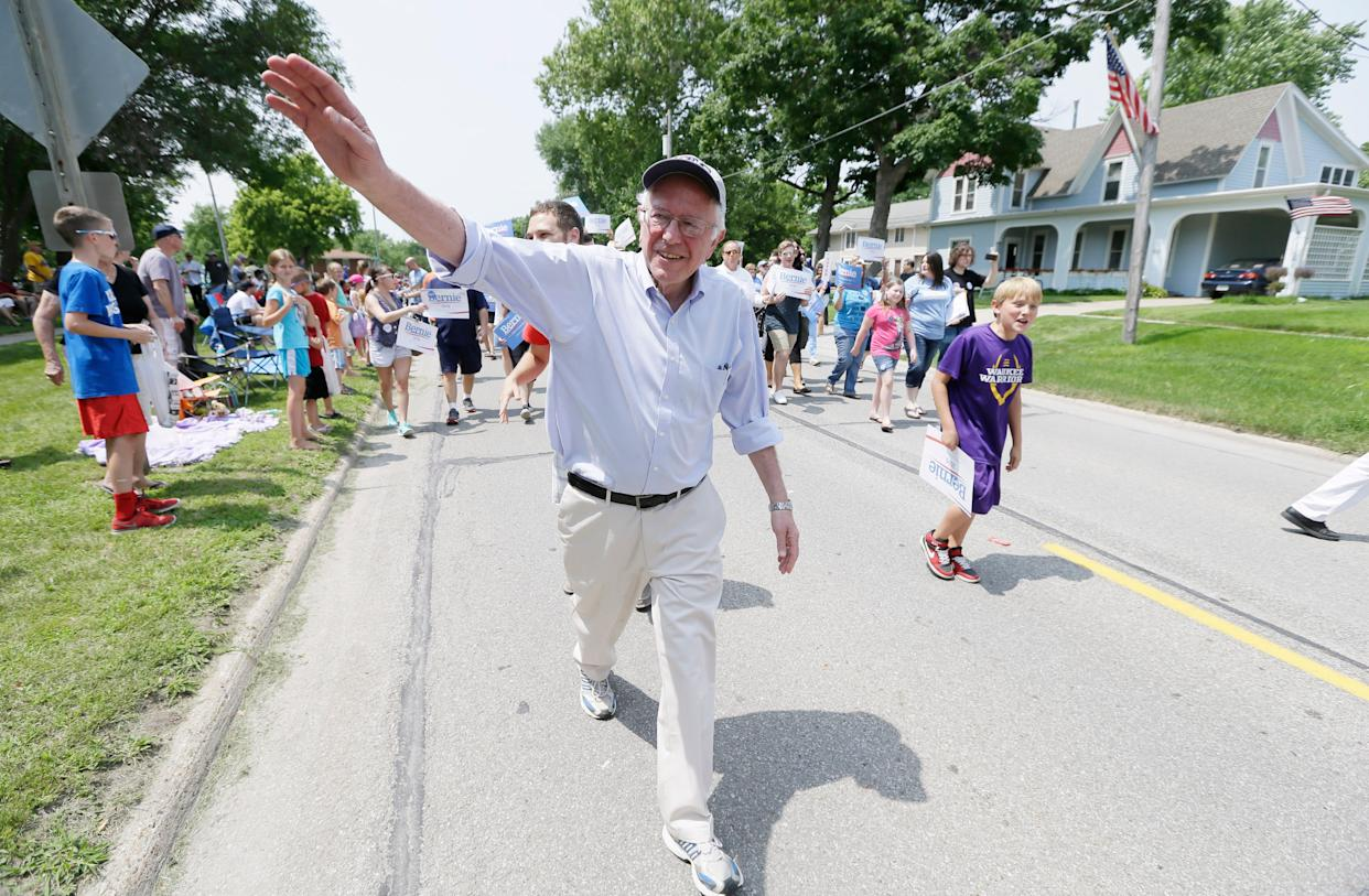 Sen. Bernie Sanders greets local residents while walking in a Fourth of July parade on Saturday, July 4, 2015 in Waukee, Iowa.