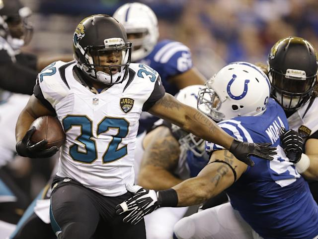 Jacksonville Jaguars' Maurice Jones-Drew (32) runs past Indianapolis Colts' Fili Moala (95) during the first half of an NFL football game Sunday, Dec. 29, 2013, in Indianapolis. (AP Photo/Michael Conroy)