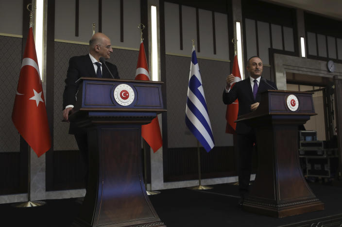 """Greek Foreign Minister Nikos Dendias, left, looks on, as Turkish Foreign Minister Mevlut Cavusoglu, right, gestures as he talks during a joint media statement following their meeting in Ankara, Turkey, Thursday, April 15, 2021. A meeting aimed to improve fraught ties between NATO allies Greece and Turkey quickly descended into a tense exchange of accusations between the two countries' foreign ministers during their media statements. Dendias accused Turkey of violating Greece's sovereign rights in the eastern Mediterranean and warned that Ankara would face European Union sanctions if the violations continue while Cavusoglu retorted back calling Dendias' words as """"unacceptable."""" The two ministers then proceeded to list their grievances.The visit was the first between the two nations following a tumultuous year. (AP Photo/Burhan Ozbilici)"""