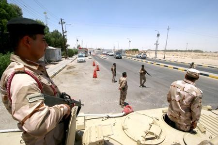 Iraqi soldiers stay guard at the entry of Zubair oilfield after a rocket struck the site of residential and operations headquarters of several oil companies in Basra