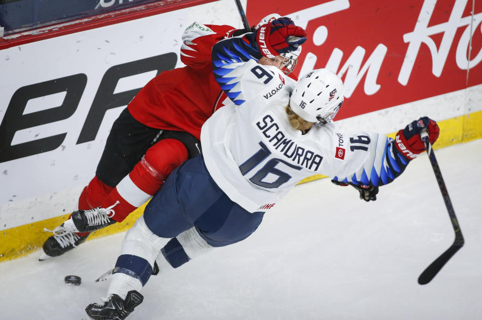 Switzerland's Nicole Vallario, left, checks Hayley Scamurra, of the United States, during the third period period of an IIHF women's hockey championship game in Calgary, Alberta, Friday, Aug. 20, 2021. (Jeff McIntosh/The Canadian Press via AP)