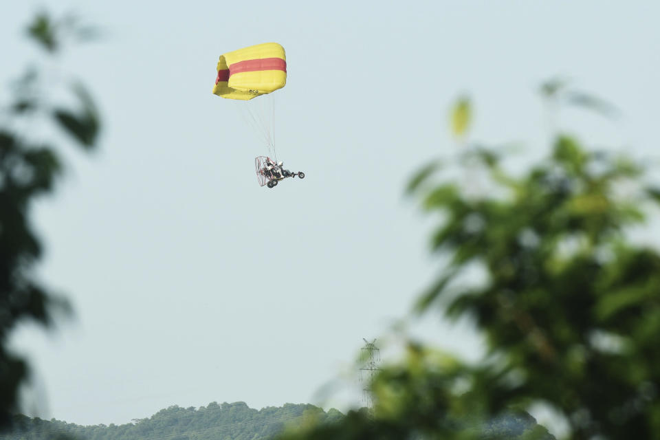 A worker in a powered parachute searches for a runaway leopard in Hangzhou in eastern China's Zhejiang province Sunday, May 9, 2021. A search for the last of three leopards that escaped from a safari park in eastern China was ongoing, authorities said Monday, May 10, 2021 as the park came under fire for concealing the breakout for nearly a week. (Chinatopix via AP)