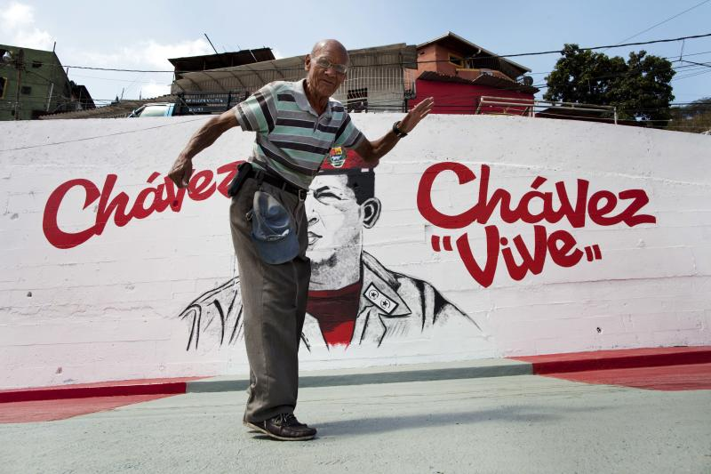 A man stops himself midstride after realizing he has walked into the framing of a picture, in front of a mural of Venezuela's late President Hugo Chavez in Caracas, Venezuela, Tuesday, March 4, 2014. He's been dead a year, but Chavez's face and voice are everywhere. He bangs out the national anthem on state radio every morning and the national guard has even blasted his voice reciting poetry to drive rock-throwing protesters off the street. To mark Chavez's passing, President Nicolas Maduro has decreed a 10-day-long commemoration - three days more than the weeklong official mourning period following his death at age 58 on March 5, 2013. (AP Photo/Rodrigo Abd)