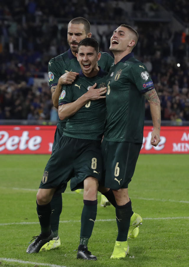 Italy's Jorginho, (8), celebrates with teammates after he scores the opening goal of the game from the penalty spot during the Euro 2020 group J qualifying soccer match between Italy and Greece in Rome, Italy, Saturday, Oct. 12, 2019. (AP Photo/Alessandra Tarantino)