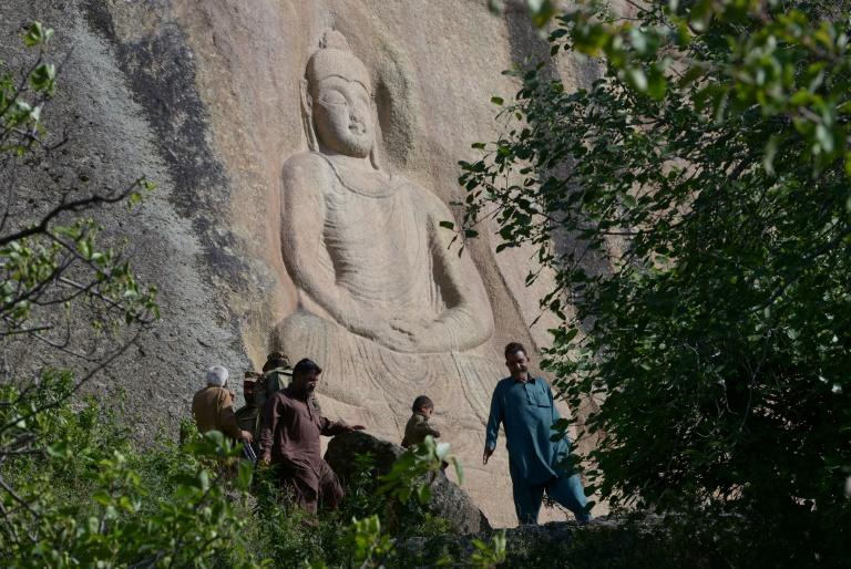 Vistors walk past the Buddha of Swat, a seventh-century sculpture carved into a mountain in the northwestern Swat Valley of Pakistan