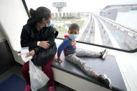 Yancarlos Amaya, 5, right, a migrant from Honduras, and his mother, Celestina Ramirez, ride a tram between terminals during a layover at George Bush International Airport, Wednesday, March 24, 2021, in Houston. A few days ago, Yancarlos was walking along a muddy river bank after crossing the Rio Grande and landing on the U.S. side of the border with Mexico. Ramirez said they turned themselves in to U.S. Border Patrol officers and later spent hours in custody, a night under a bridge and three more days in a detention facility. (AP Photo/Julio Cortez)