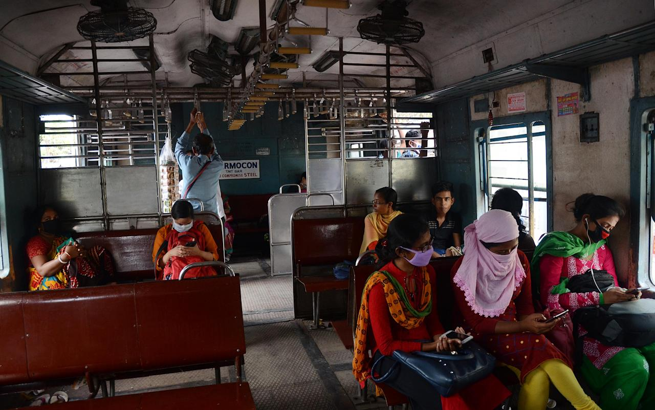 Passengers wearing facemasks amid concerns over the spread of the COVID-19 novel coronavirus, disease pandemic during travel at local train in Kolkata, India on March 21, 2020. Sixty cases were reported from country on Friday the most in one day as the number of coronavirus cases rose to 283 in the country. (Photo by Sonali Pal Chaudhury/NurPhoto via Getty Images)