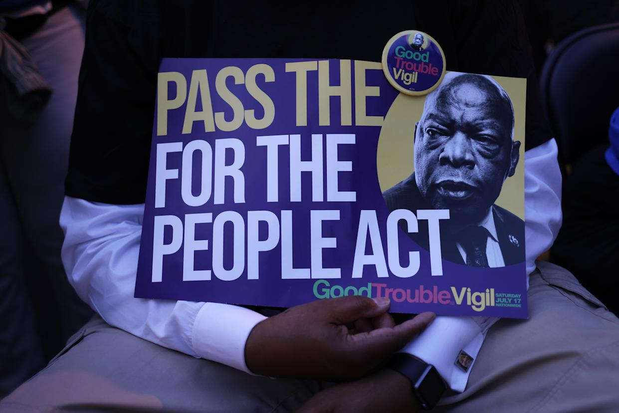 A voting rights activist holds a sign that reads