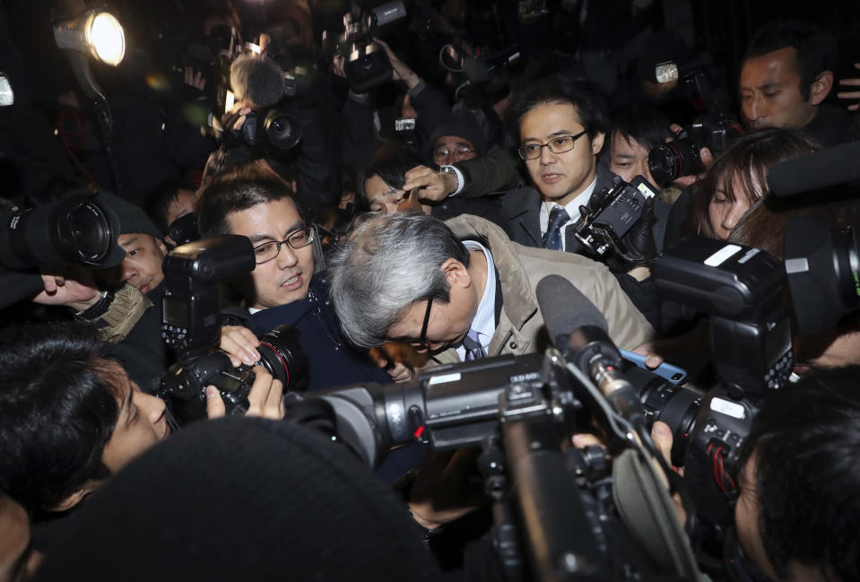 Motonari Otsuru, center, defense lawyer of former Nissan chairman Carlos Ghosn, is surrounded by journalists as he leaves from Tokyo Detention Center where Ghosn and another former executive Greg Kelly are being detained, in Tokyo, Thursday, Dec. 20, 2018. The Tokyo District Court on Thursday rejected the request for another 10-day detention over Ghosn's indictment for falsification of financial reports. (AP Photo/Eugene Hoshiko)