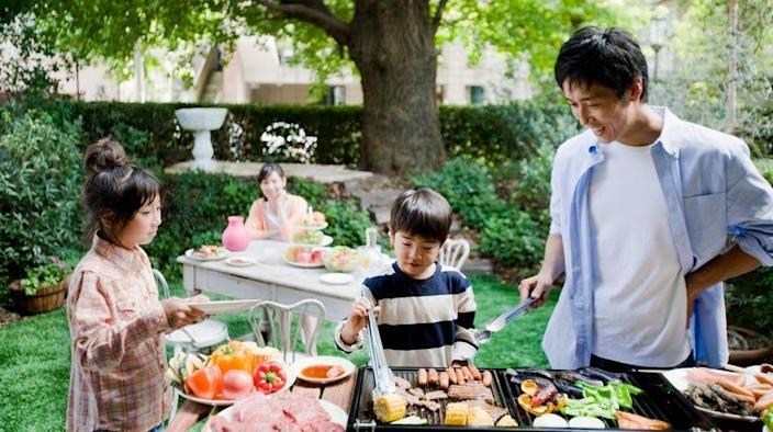 Father cooking on outdoor grill with children