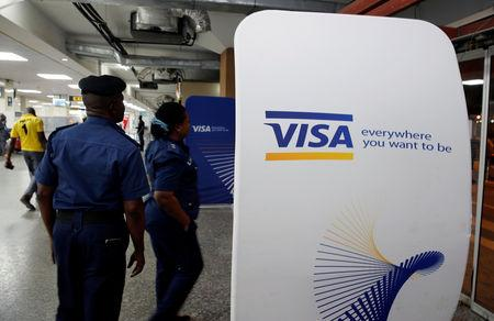 Security staff stand next to a Visa logo at Murtala Muhammed International Airport before the arrival of the Nigerian Women's Bobsled Team, in Lagos
