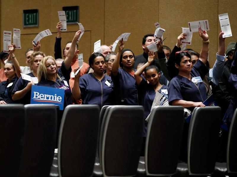 Casino workers hold up presidential preference cards as they support Democratic presidential candidate Bernie Sanders during a presidential caucus at the Bellagio hotel-casino: AP