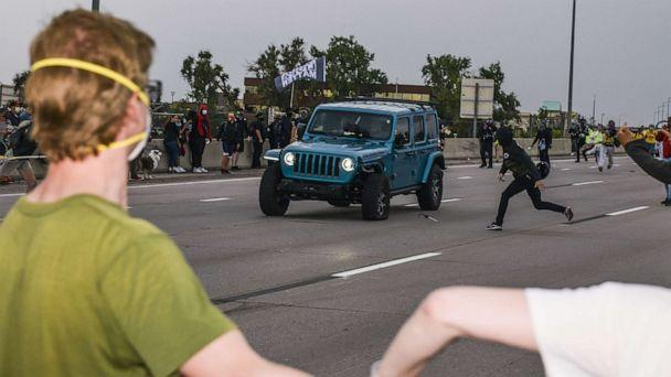 PHOTO: People run to get out of the way as a Jeep speeds through a crowd of people protesting the death of Elijah McClain on I-225 on July 25, 2020 in Aurora, Colorado. (Michael Ciaglo/Getty Images)