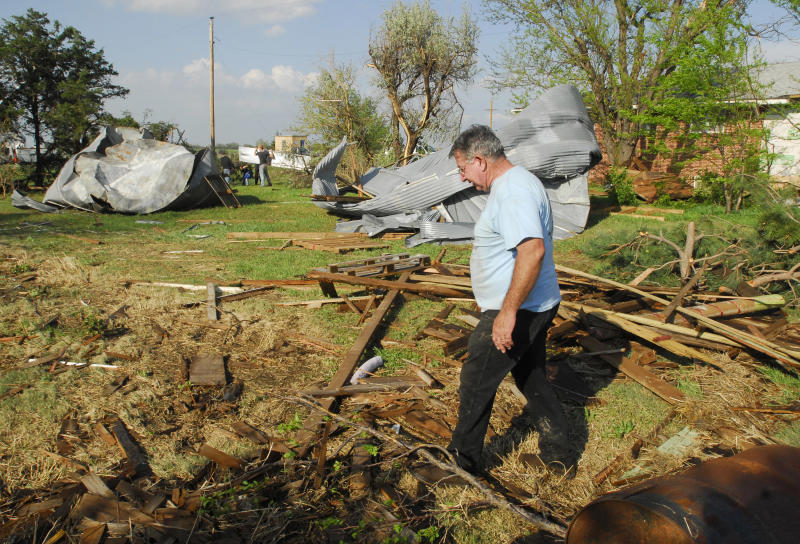 Blaine Hyatt, Rush Center, walks around his yard on Saturday, April 14, 2012, about a mile east of Rush Center, Kan., after a tornado damaged his home, destroyed several outbuildings and two grain bins. (AP Photo/The Hays Daily News, Steven Hausler)