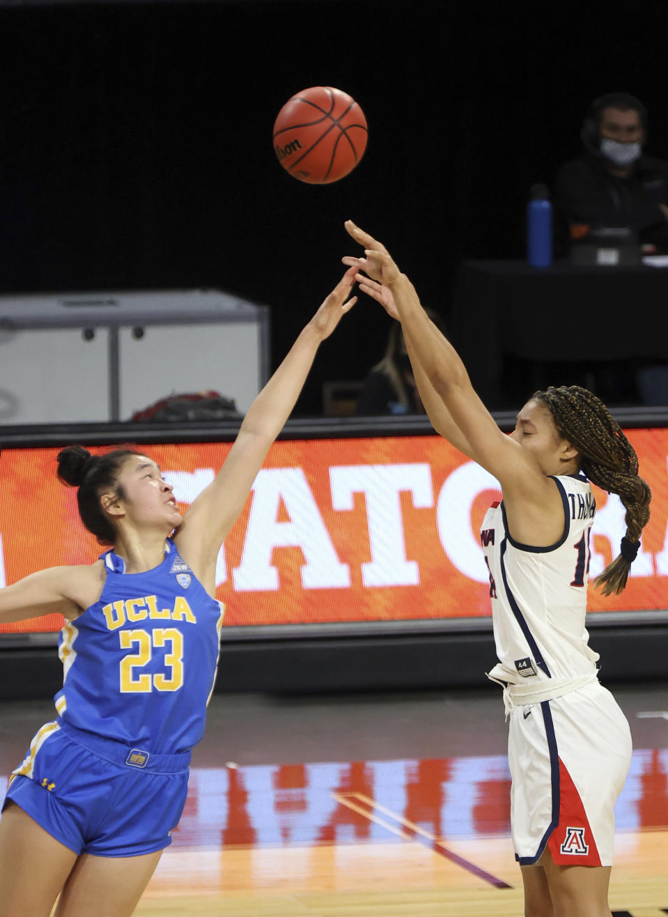 Arizona forward Sam Thomas (14) shoots as UCLA guard Natalie Chou (23) defends during the first half of an NCAA college basketball game in the semifinals of the Pac-12 women's tournament Friday, March 5, 2021, in Las Vegas. (AP Photo/Isaac Brekken)