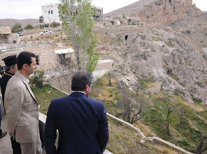 """In this photo released by the Syrian official news agency SANA, Syrian President Bashar Assad, center, tours the Christian village of Maaloula, near Damascus, Syria, Sunday April, 20, 2014. Assad visited a historic Christian village his forces recently captured from rebels, state media said, as the country's Greek Orthodox Patriarch vowed that Christians in the war-ravaged country """"will not submit and yield"""" to extremists. The rebels, including fighters from the al-Qaida-affiliated Nusra Front, took Maaloula several times late last year. (AP Photo/SANA)"""