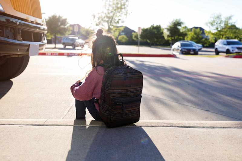 An unknown schoolgirl with a backpack hugs her knees and sits on the curb by herself at a bus stop, while the bus is parked nearby.