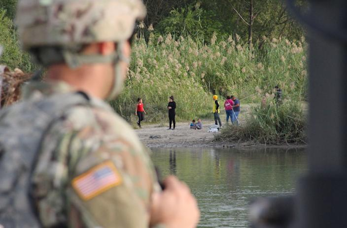 A soldier from Kentucky looks across the Rio Grande from Laredo, Texas, toward Nuevo Laredo, Mexico, at a group of people on the riverbank on Nov. 17, 2018. (Photo: Thomas Watkins/AFP/Getty Images)