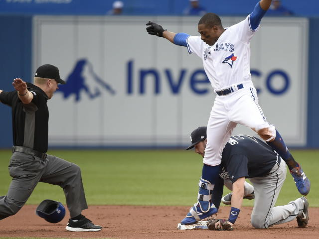 Toronto Blue Jays' Curtis Granderson, top, is safe with a double as Atlanta Braves shortstop Dansby Swanson is late on the tag during the first inning of a baseball game Tuesday, June 19, 2018, in Toronto. (Nathan Denette/The Canadian Press via AP)