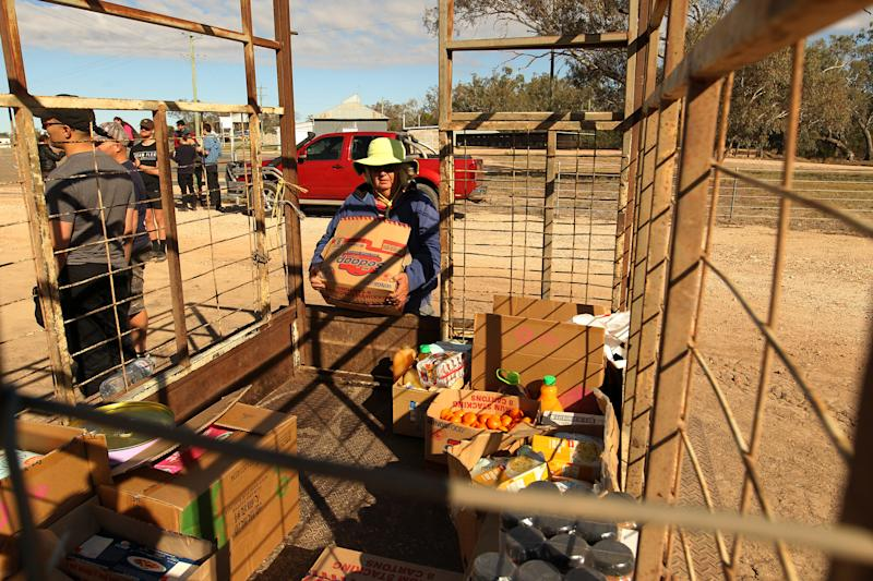 Bessie Lambert is seen loading a trailer with food and water aid in the drought-stricken NSW/QLD border town of Mungindi, NSW.