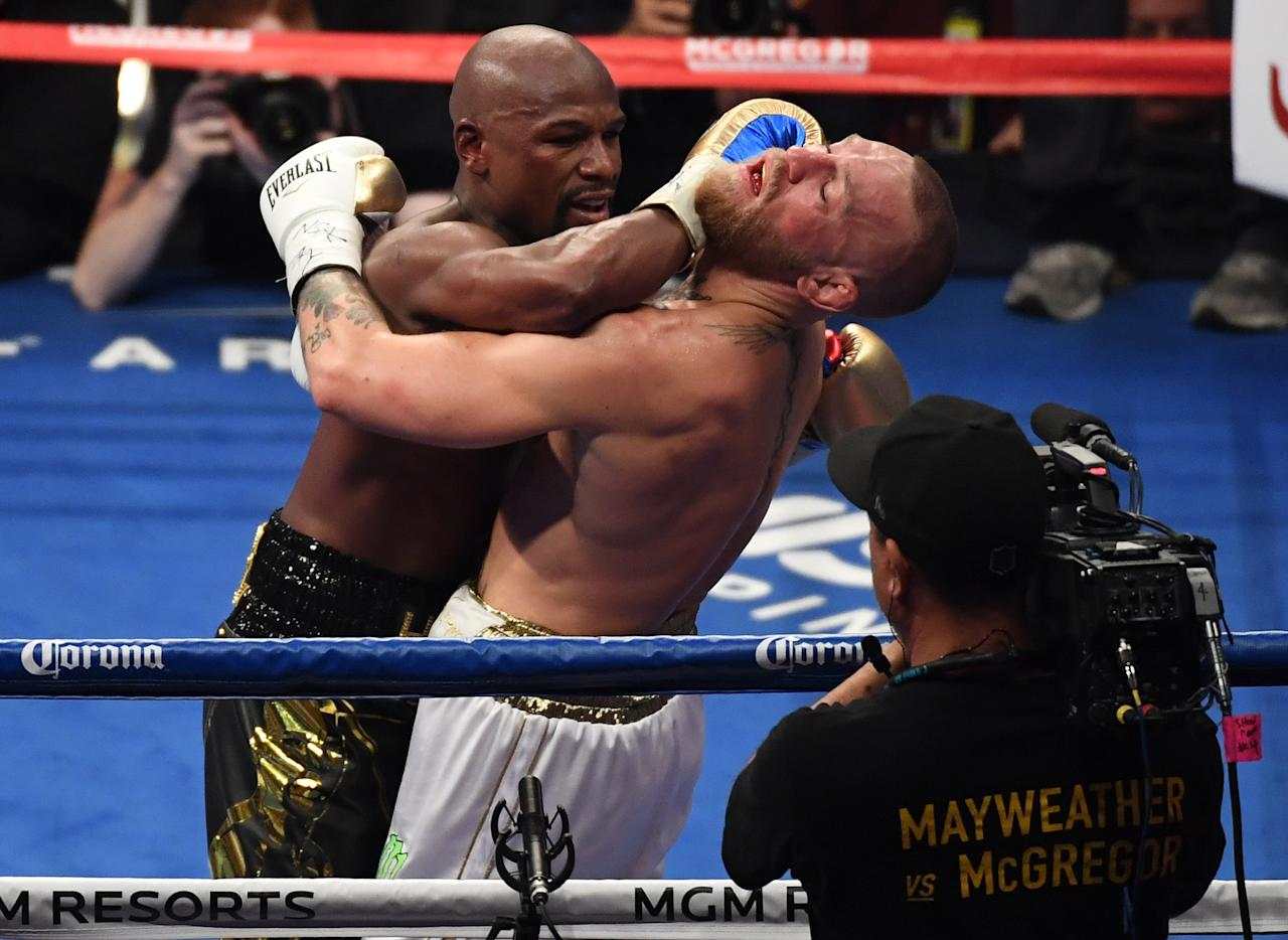 <p>(L-R) Floyd Mayweather Jr. throws a punch at Conor McGregor during their super welterweight boxing match on August 26, 2017 at T-Mobile Arena in Las Vegas, Nevada. </p>