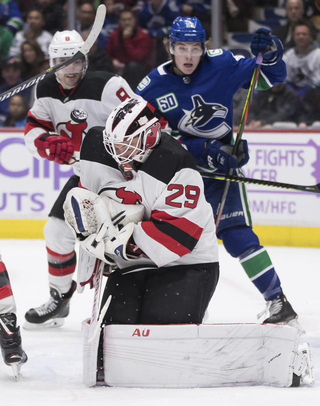 New Jersey Devils goalie MacKenzie Blackwood (29) makes a save as Will Butcher, back left, and Vancouver Canucks' Adam Gaudette watch during the second period of an NHL hockey game in Vancouver, British Columbia, Sunday, Nov. 10, 2019. (Darryl Dyck/The Canadian Press via AP)