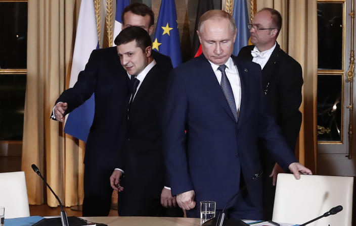 FILE - In this Dec. 9, 2019, file photo, Russian President Vladimir Putin, right, and Ukrainian President Volodymyr Zelenskiy arrive for a working session at the Elysee Palace, Paris, France. The leaders of Russia, Ukraine, France and Germany reaffirmed their commitment to a 2015 peace deal for eastern Ukraine. (Ian Langsdon/Pool Photo via AP, File)
