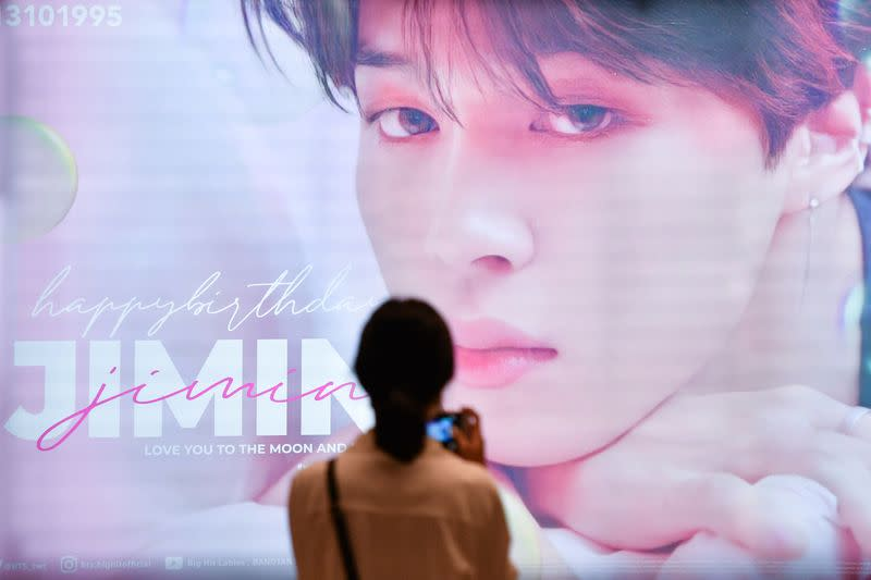 A woman takes a picture of a billboard whishing happy birthday to a K-pop singer Jimin at the subway in Bangkok