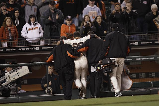 FILE - In this May 25, 2011, file photo, San Francisco Giants catcher Buster Posey (28) is helped from the field after a home plate collision with Florida Marlins' Scott Cousins during the 12th inning of a baseball game in San Francisco. New York Mets general manager Sandy Alderson, chairman of the rules committee, announced Wednesday, Dec. 11, 2013, that Major League Baseball plans to eliminate home plate collisions. He said player health and increased awareness of concussions were behind the decision. (AP Photo/Marcio Jose Sanchez, File)