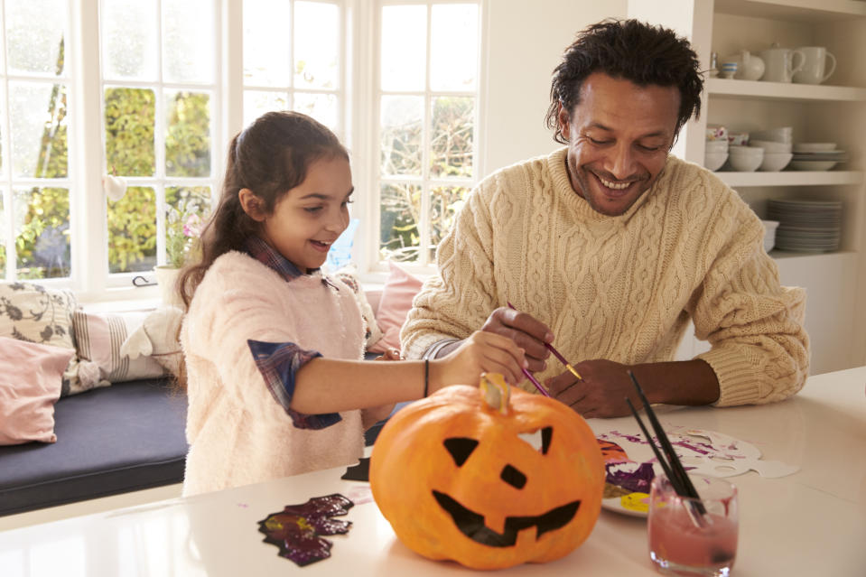 Father And Daughter Making Halloween Decorations At Home