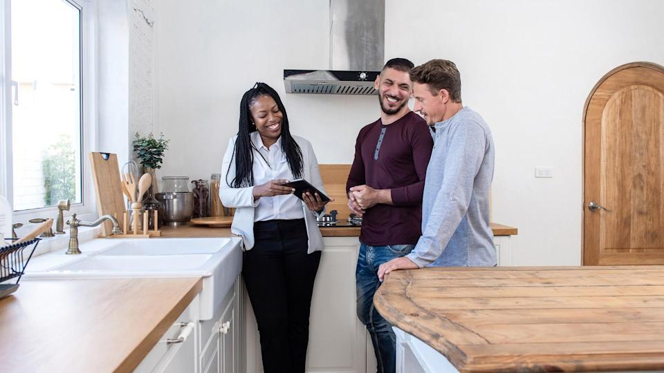African american female real estate agent in kitchen showing gay couple around new house.