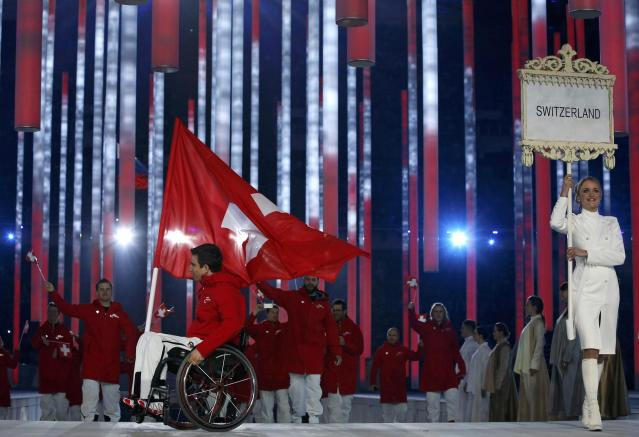Switzerland's flag-bearer Christoph Kunz (L), leads his country's contingent during the opening ceremony of the 2014 Paralympic Winter Games in Sochi, March 7, 2014. REUTERS/Alexander Demianchuk (RUSSIA - Tags: OLYMPICS SPORT)