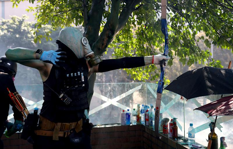 An anti-government protester uses a bow during clashes with police outside Hong Kong Polytechnic University (PolyU), in Hong Kong, China, November 17, 2019. REUTERS/Athit Perawongmetha