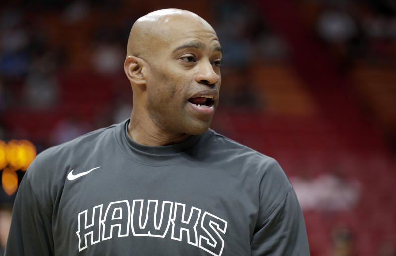 "Vince Carter in a gray ""HAWKS"" warm-up shirt."