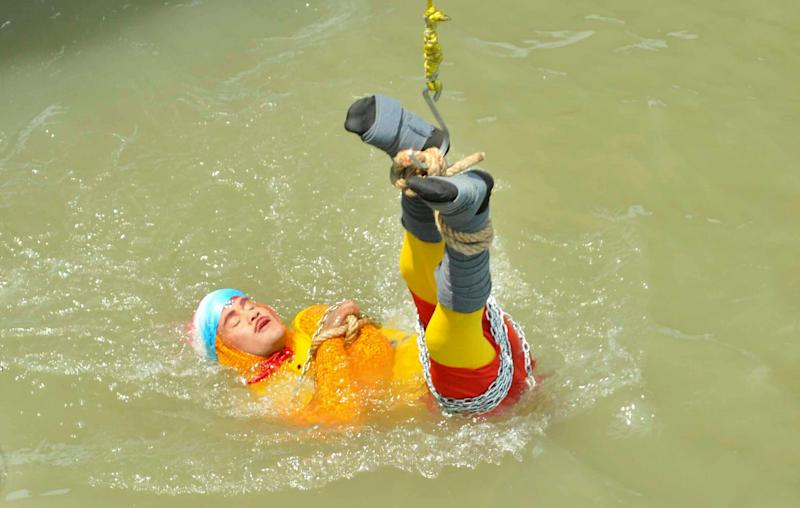 Magician Chanchal Lahiri is lowered into the Hooghly river in Kolkata on Sunday before attempting what would turn out to be his last ever stunt (Picture: Reuters)