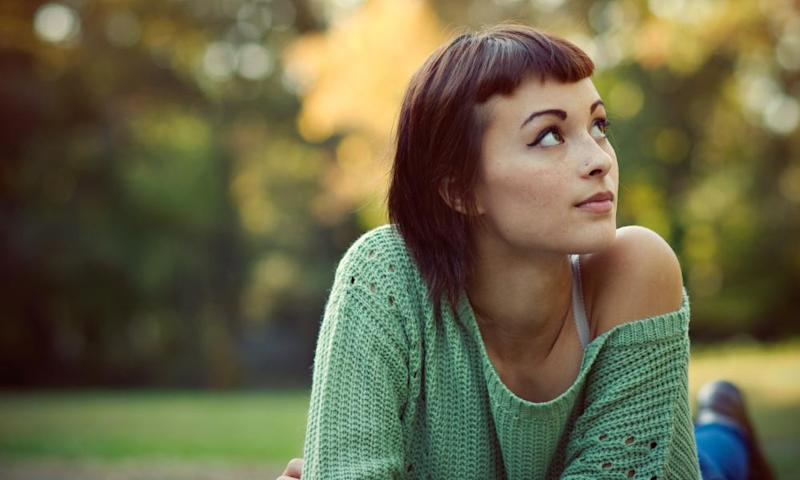 Young woman looking up with autumn background<br>Young woman with short bangs and green sweater looking up with bright autumn background.