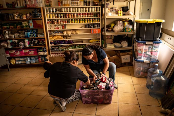 "Shelter volunteer Marta Leticia Galarza Gandara, right, helps Isa find shoes for her baby daughter in a box of donations. Isa is an asylum seeker from Honduras, and has been waiting at the border under MPP since September 2019.<span class=""copyright"">Meridith Kohut for TIME</span>"