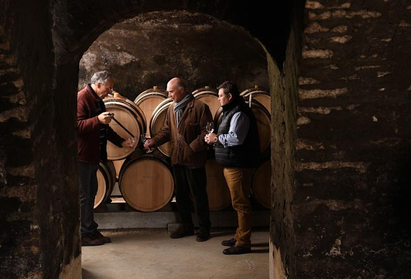 Leading figure of the Burgundy winegrowers, co-heir and co-manager of the estate of La Romanee Conti, Aubert de Villaine (C), his nephew Bertrand de Villaine (R) and chief of the cellars Bernard Noblet taste wine in a cellar on January 9, 2018 in Vosnes Romanee (Burgondy). / AFP PHOTO / Eric FEFERBERG (Photo credit should read ERIC FEFERBERG/AFP/Getty Images)