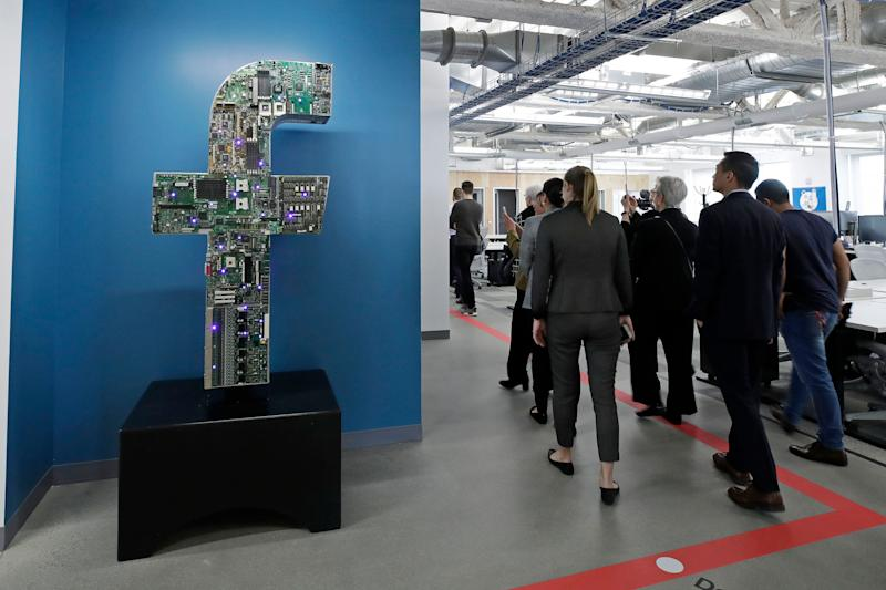 In this Jan. 9, 2019 photo, media and guests tour Facebook's new 130,000-square-foot offices, which occupy the top three floors of a 10-story Cambridge, Mass. building. The space gives the company room to triple its current local staff of more than 200. The Silicon Valley company, created by Mark Zuckerberg when he was two subway stops away at Harvard University, opened its first Boston office five years ago. (AP Photo/Elise Amendola)