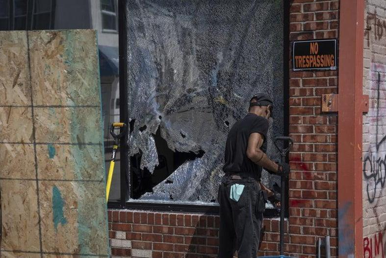 <p>A man cleans up a broken window to a barber shop after shots were fired in George Floyd Square on the one year anniversary of Mr Floyd's death</p> (AP)