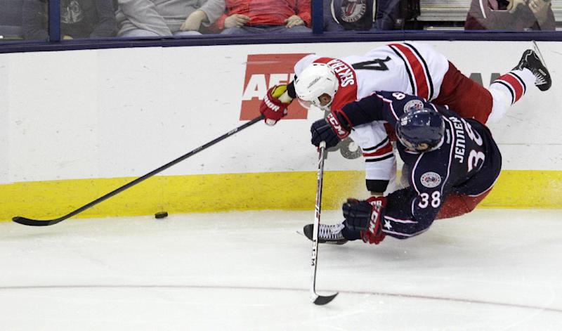 Carolina Hurricanes' Andrej Sekera, top, of Slovakia and Columbus Blue Jackets' Boone Jenner chase a loose puck during the third period of an NHL hockey game on Thursday, Sept. 26, 2013, in Columbus, Ohio. The Hurricanes defeated the Blue Jackets 2-1. (AP Photo/Jay LaPrete)