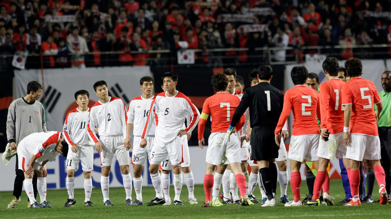 FILE - In this April 1, 2009, file photo, North Korean players, wearing white uniforms, shake hands with South Korean players after their 2010 FIFA World Cup Asia group 2 qualifying soccer match at Seoul World Cup Stadium in Seoul, South Korea. The South Korean men's national soccer team's path to the 2022 World Cup in Qatar will include a crucial road match against North Korea, but it's unclear whether a rare match between the Koreas in Pyongyang will materialize considering the political tension between the rivals. (AP Photo/Lee Jin-man, File)
