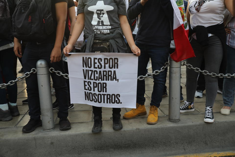 "A woman, holding a sign with a message that reads in Spanish: ""It's not for Vizcarra, it's for us,"" joins others outside the Justice Palace where people who are refusing to recognize the new government gathered to protest, in Lima, Peru, Wednesday, Nov. 11, 2020. On Tuesday, Peru swore in Manuel Merino as president, after Peru's legislature booted President Martin Vizcarra from office on Monday. (AP Photo/Rodrigo Abd)"